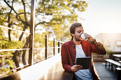 Buy stock photo Cropped shot of a handsome young man using his digital tablet while drinking coffee outside