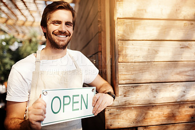 Buy stock photo Cropped portrait of a handsome young male business owner holding up a sign in the doorway of his coffee shop