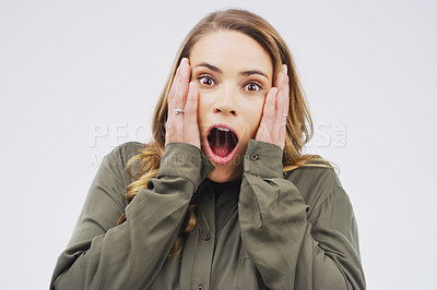 Buy stock photo Studio portrait of an attractive young woman looking shocked against a grey background