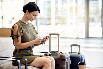 Buy stock photo Shot of a cheerful young businesswoman texting on her cellphone while waiting for her flight at a airport