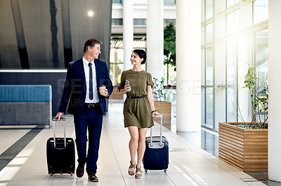 Buy stock photo Shot of two confident businesspeople walking together with their luggage and drinking coffee inside of an airport