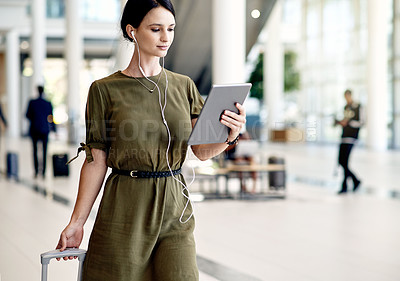 Buy stock photo Shot of a confident young businesswoman walking with a digital tablet and dragging her luggage inside of a airport during the day