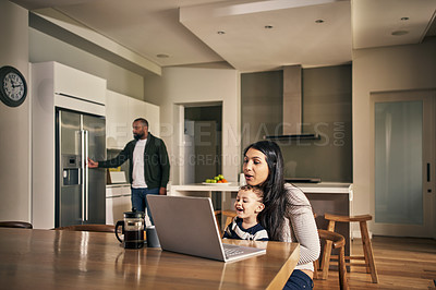 Buy stock photo Shot of a young woman using a laptop wth her adorable son at home