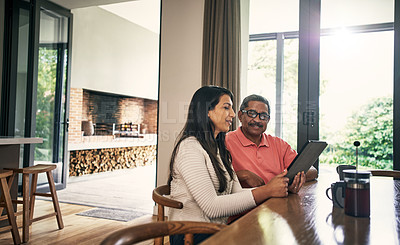 Buy stock photo Shot of a young woman using a laptop with her father at home