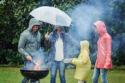 Buy stock photo Shot of a young family of four having a barbecue outside in the rain