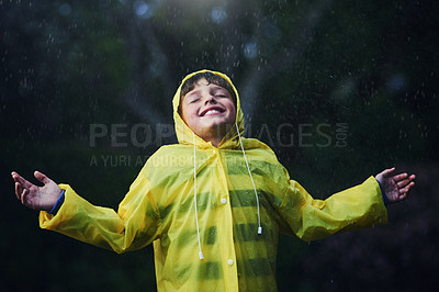 Buy stock photo Shot of a young boy playing outside in the rain