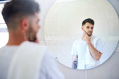 Buy stock photo Shot of a young man examining his face in the bathroom at home