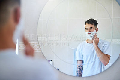 Buy stock photo Shot of a young man applying shaving cream to his face in the bathroom at home