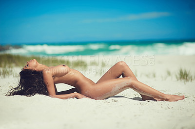 Buy stock photo Full body shot of a young woman laying naked on sand at the beach