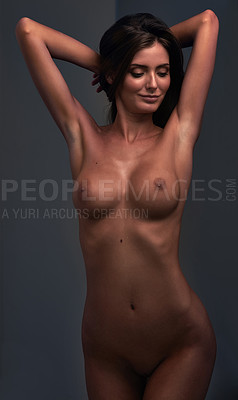 Buy stock photo Studio portrait of a beautiful young woman posing nude against a dark background