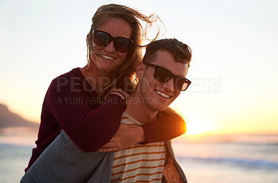 Buy stock photo Cropped portrait of an affectionate young man piggybacking his girlfriend at the beach