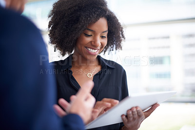 Buy stock photo Cropped shot of two businesspeople discussing work over a tablet in their office