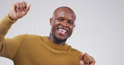 Buy stock photo Studio portrait of a handsome young man feeling cheerful and dancing against a grey background