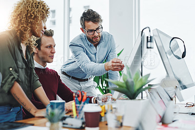 Buy stock photo Shot of a group of colleagues using a computer together in a modern office