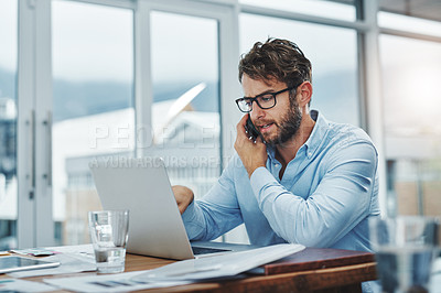 Buy stock photo Shot of a young businessman using a phone and laptop at his desk in a modern office