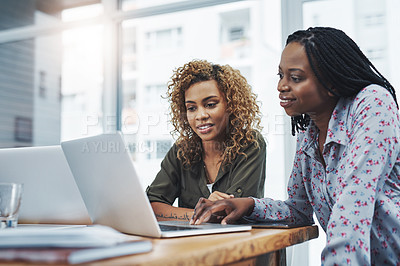 Buy stock photo Shot of two young colleagues using a laptop together in a modern office