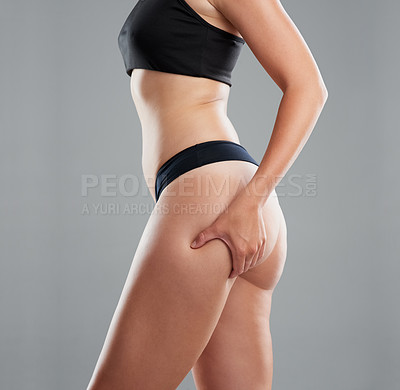 Buy stock photo Studio shot of an unrecognizable woman pinching her thigh against a grey background