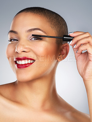 Buy stock photo Studio shot of a beautiful young woman applying mascara against a grey background