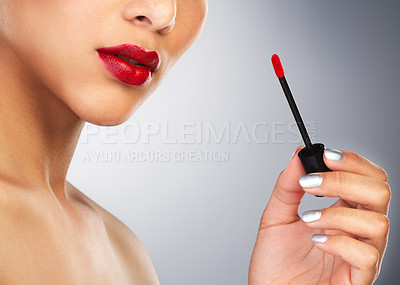Buy stock photo Cropped shot of an unrecognizable woman applying red lipstick to her lips