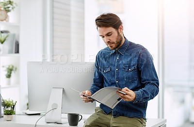 Buy stock photo Shot of a young businessman looking through a report in his office