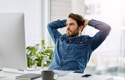 Buy stock photo Shot of a young businessman looking thoughtful with his hands behind his head in his office