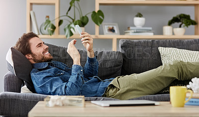 Buy stock photo Shot of a young man using his mobile phone while laying on his couch at home