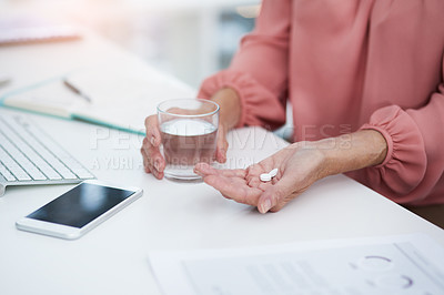 Buy stock photo Shot of an unrecognizable senior woman taking her medication at her office desk at work