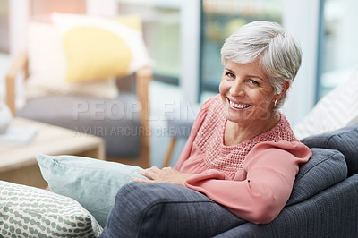 Buy stock photo Shot of a cheerful mature woman relaxing on a sofa at home