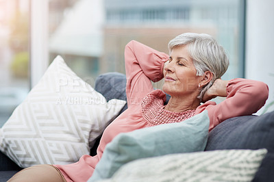 Buy stock photo Shot of cheerful mature woman laid back and relaxing on her sofa at home