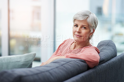 Buy stock photo Portrait of a cheerful mature woman relaxing on her sofa at home