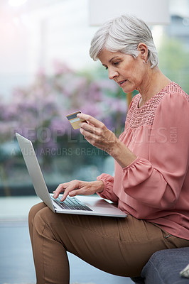 Buy stock photo Shot of a mature woman using her laptop while holding her credit card at home