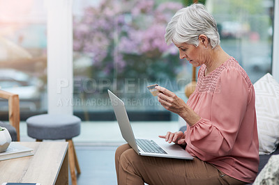 Buy stock photo Shot of a mature woman sitting on a couch and using her laptop to do some online shopping at home