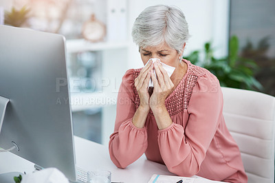 Buy stock photo Shot of a mature businesswoman blowing her nose while sitting at her office desk at work