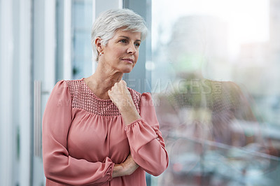 Buy stock photo Shot of a mature businesswoman looking thoughtful in her office at work