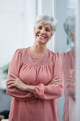 Buy stock photo Portrait of a cheerful mature businesswoman posing with her arms folded in her office at work