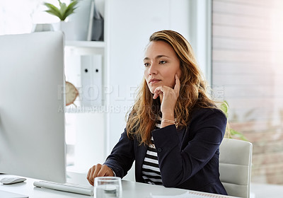 Buy stock photo Shot of an attractive businesswoman looking thoughtful while working on a computer in her office