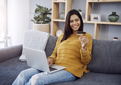 Buy stock photo Shot of an attractive young woman doing some online shopping on her laptop while relaxing on a sofa at home