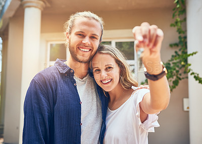 Buy stock photo Portrait of a young couple holding the keys to their new home