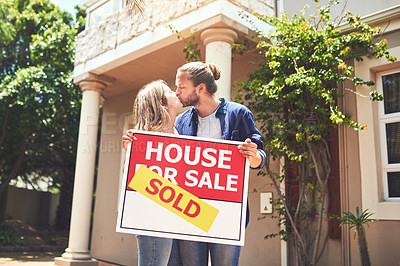 Buy stock photo Shot of a young couple holding a sign outside their new home