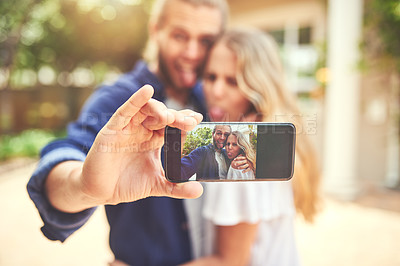 Buy stock photo Shot of a young couple taking selfies outside their new home