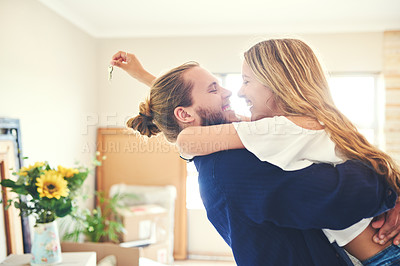 Buy stock photo Shot of a young couple celebrating the move into their new home