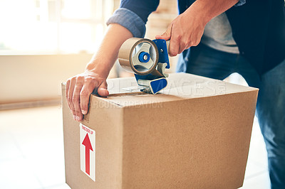 Buy stock photo Closeup shot of a man sealing a box with tape