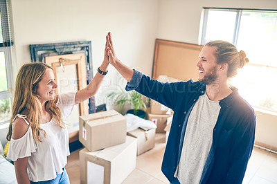 Buy stock photo Shot of a young couple giving each other a high five while moving in to their new home