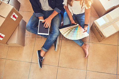 Buy stock photo High angle shot of a couple using a digital tablet while looking at color swatches in their new home