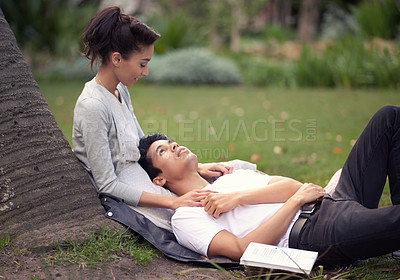 Buy stock photo Shot of a beautiful young couple spending some time together at the park