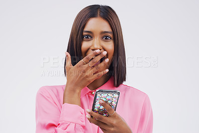Buy stock photo Studio shot of a young woman looking surprised while reading something on her cellphone