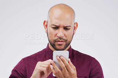 Buy stock photo Studio shot of a handsome man using his cellphone against a grey background