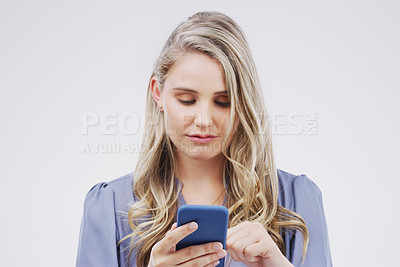Buy stock photo Studio shot of a beautiful young woman using her cellphone against a grey background