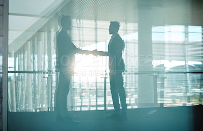 Buy stock photo Shot of two businessmen shaking hands in a modern workplace