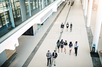 Buy stock photo High angle shot of a group businesspeople walking through a modern workplace